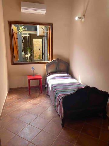 Dormitorio número 2. Cama soltero. Vista e iluminación al jardín interior
