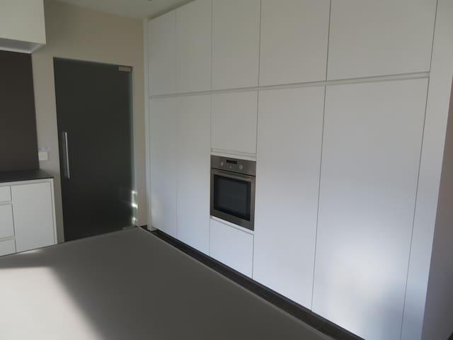 Keukenwand met microgolf, oven en frigo.
