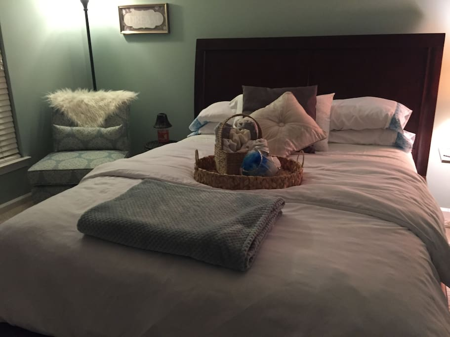 Luxury queen size bed, soft lighting and comfy sitting chair surrounded by plush white flokati rugs welcoming accessories.