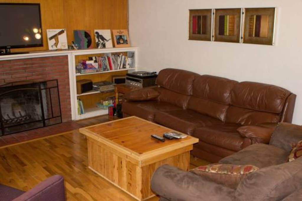 "The living room with hard wood floor, fire place, 40"" television, record player and plenty of seating."