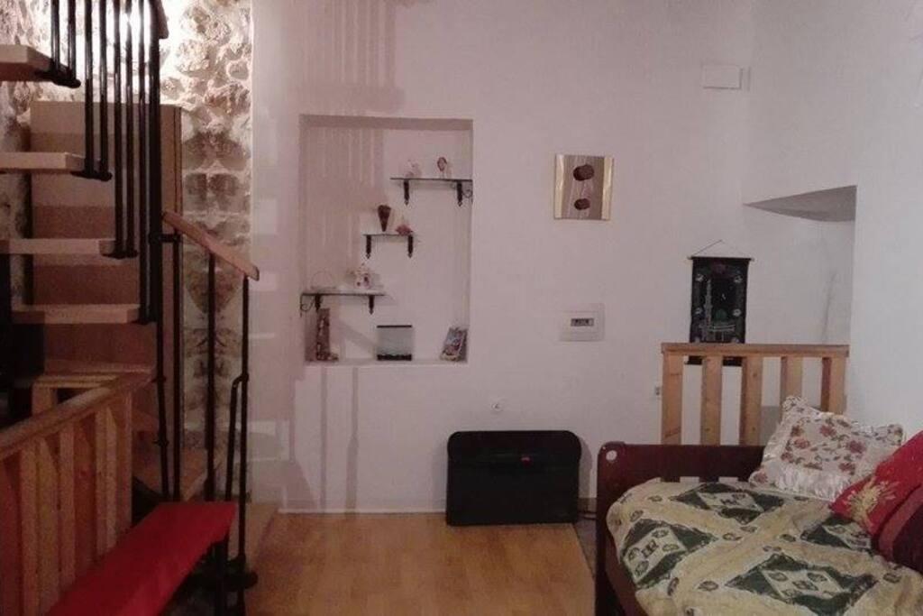 salotto con ingresso e scala di legno che conduce alla camera del piano superiore