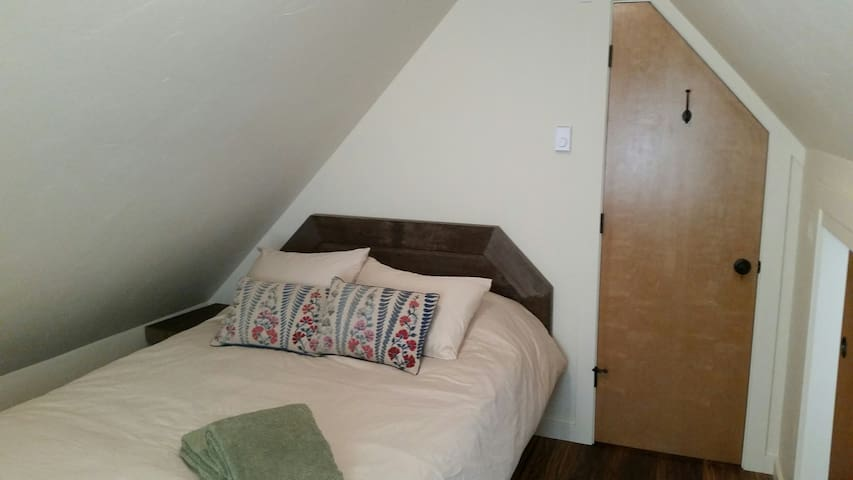 Cozy, comfy upstairs bedroom with views of the trees and a cozy fireplace heater.