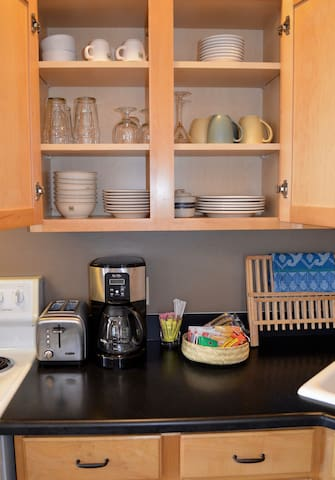 The kitchen is fully stocked with dishes, cookware, and all the basics you'll need to prepare meals.