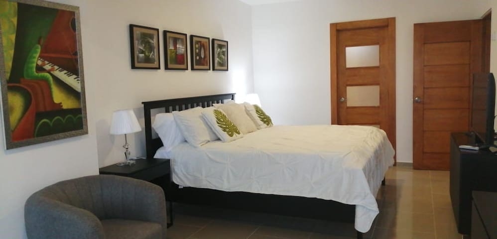 A beautiful master bedroom offering a king size bed with tv and a sitting area. Looking out to the balcony with a sea view.