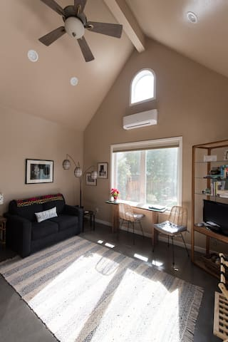 Living Area has 18' ceiling & dining table/workspace