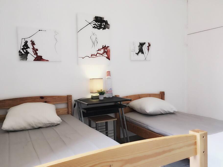 Chambre privée avec deux lit séparé, table, chaise, lumineux et propre.