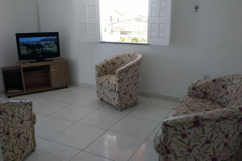"""Uma sala de estar, com um conjunto de sofá,  TV 42"""" e rede de casal."""