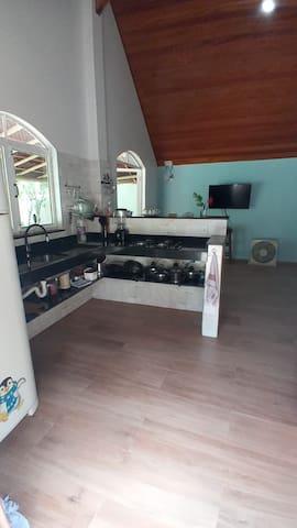cozinha com geladeira, fogão cooktop e ultencilios, sala com TV ( parabólica) e um sofá pequeno