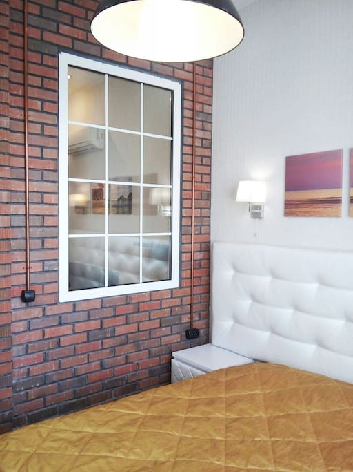 Bedroom is divided from the other space by loft-styled brick wall