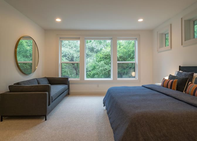 Master bedroom on the second floor with a king bed, sofa, and full bathroom with stand up shower