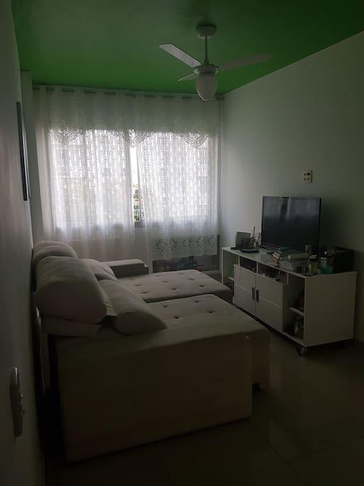 sala com sofá retrátil, ventilador e tv