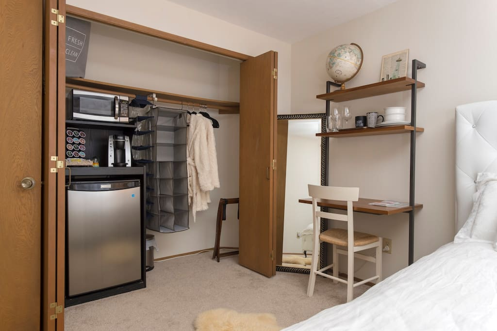 First bedroom - queen bed, desk, chair, mini fridge, Keurig coffee machine, microwave, cutlery, bowls, plates, luggage rack, full length mirror, hangers, alarm clock and soft guest bathrobes