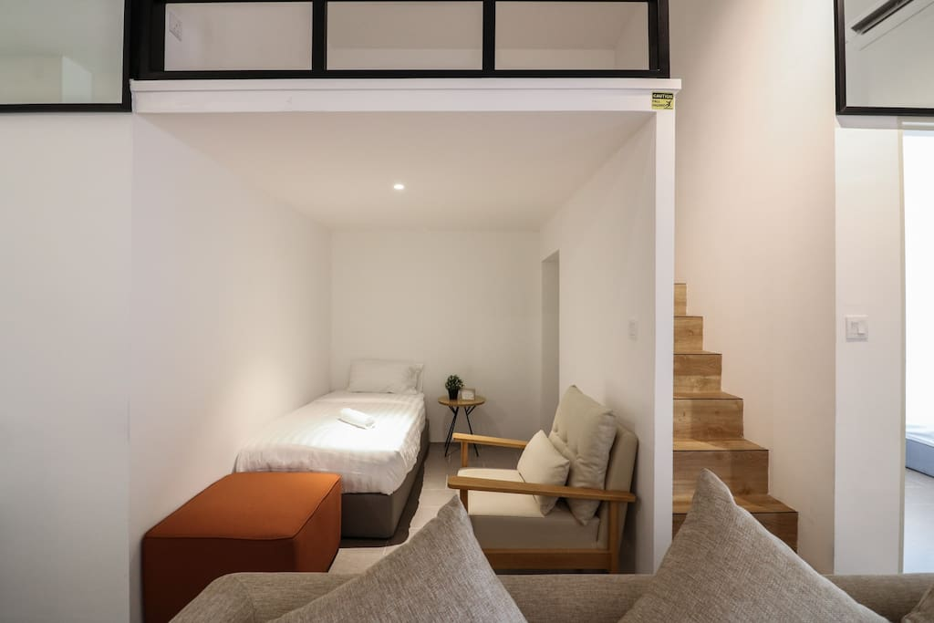 Single bed and relax area under loft