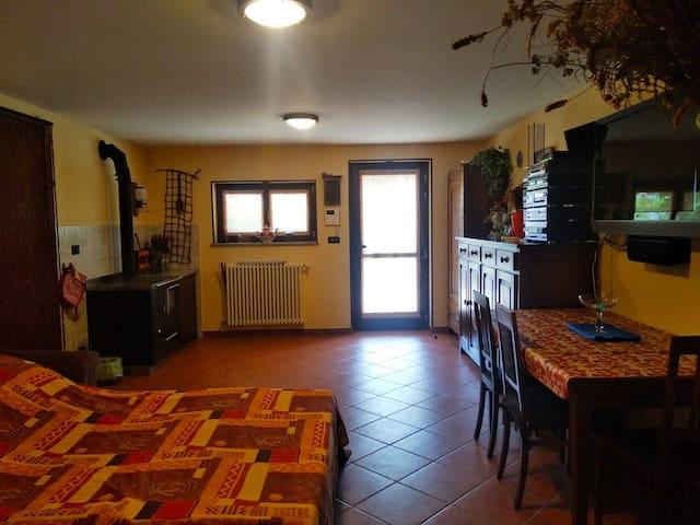 Vista della camera con ingresso e finestra, con divano-letto aperto. Sulla destra lo schermo TV, tavolo, credenza, armadio.