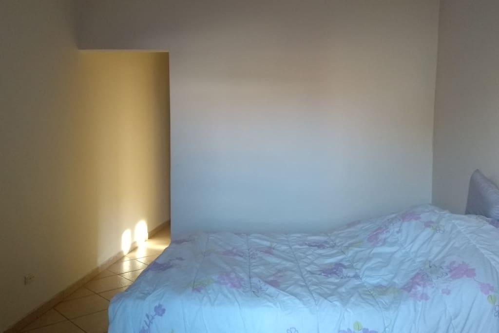 Quarto com cama de casal com TV e varanda