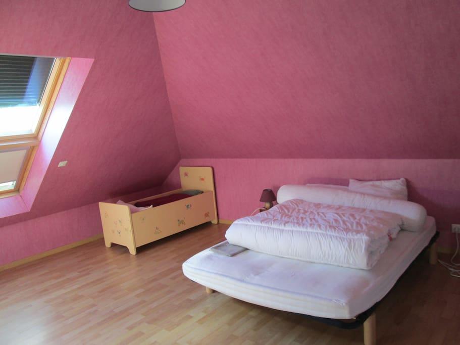 Chambre d'environ 25m² avec un lit double et un lit d'enfant/bébé, possibilité d'ajouter un lit simple supplémentaire.