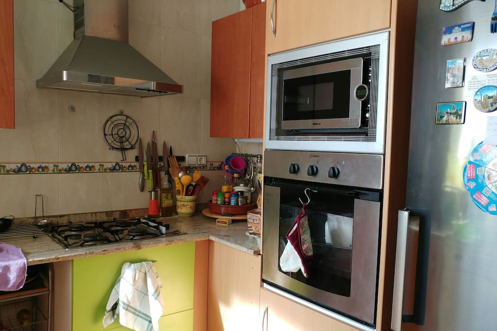 modern kitchen with microwave, oven, new fridge.