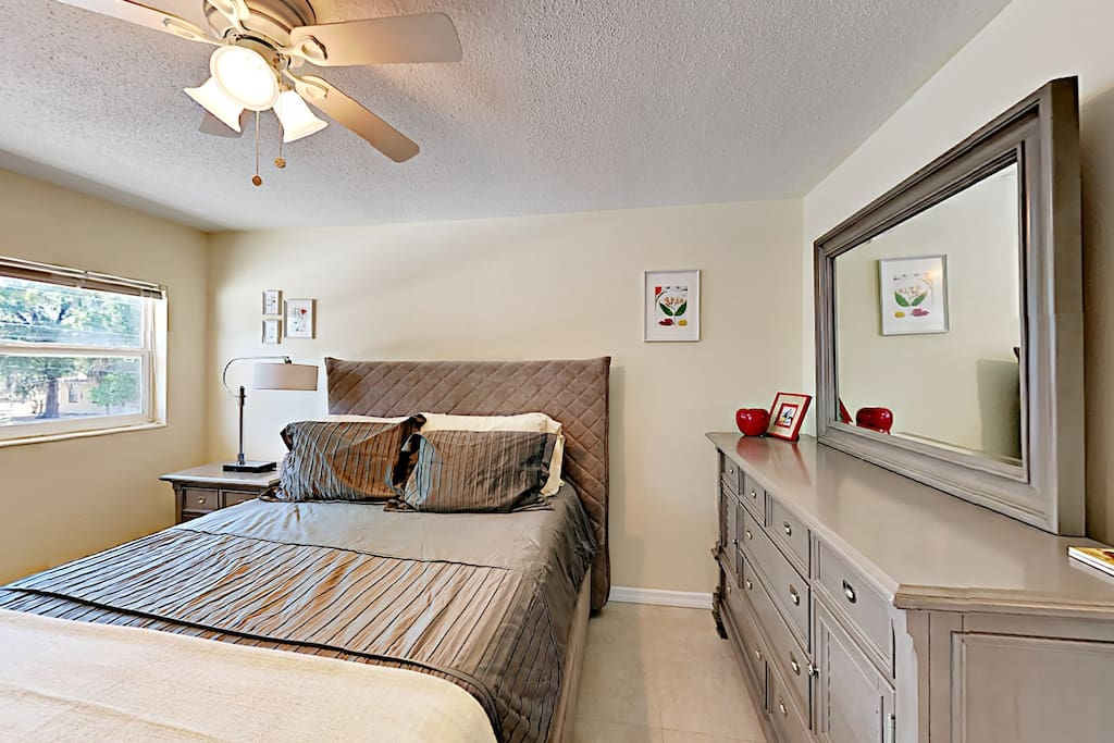 The bedroom features a queen bed and contemporary furnishings.