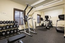 24-Hour Fitness Center with free weights, treadmill, elliptical, towels, water station, and bathroom with shower.