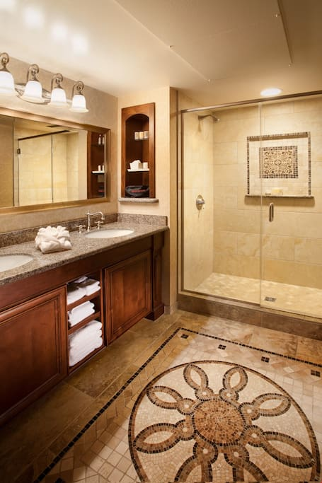 The spacious natural stone bathroom features a glass-enclosed shower and comes fully-equipped with plush bathrobes and Fresh brand amenities