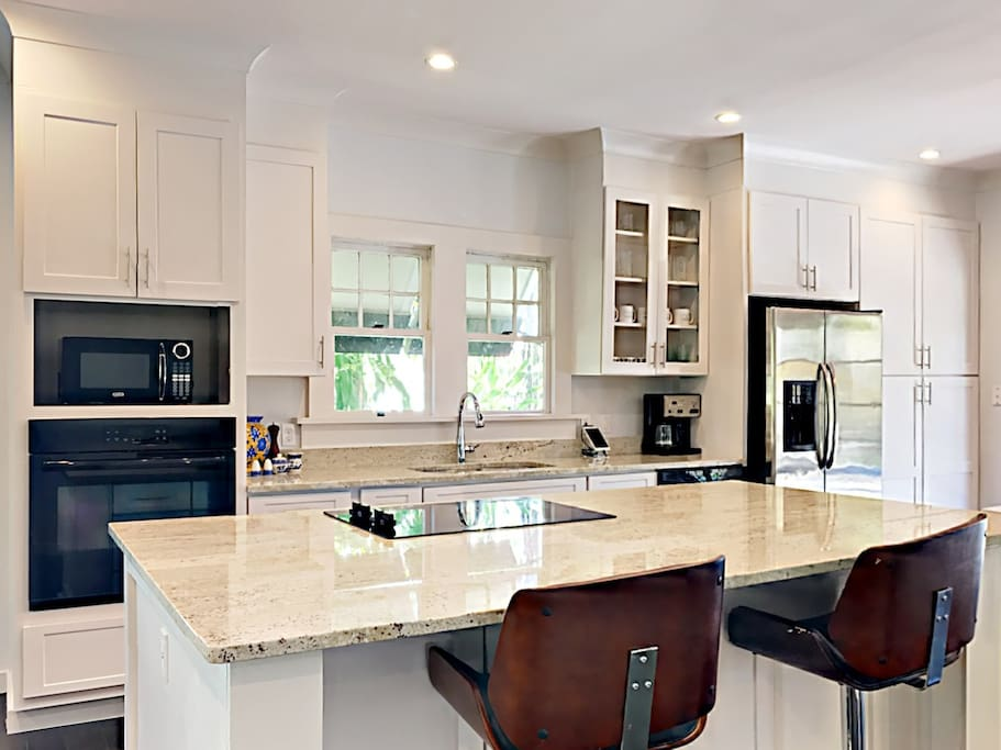 Open to the living room, the kitchen delights with a granite center island with seating for two.