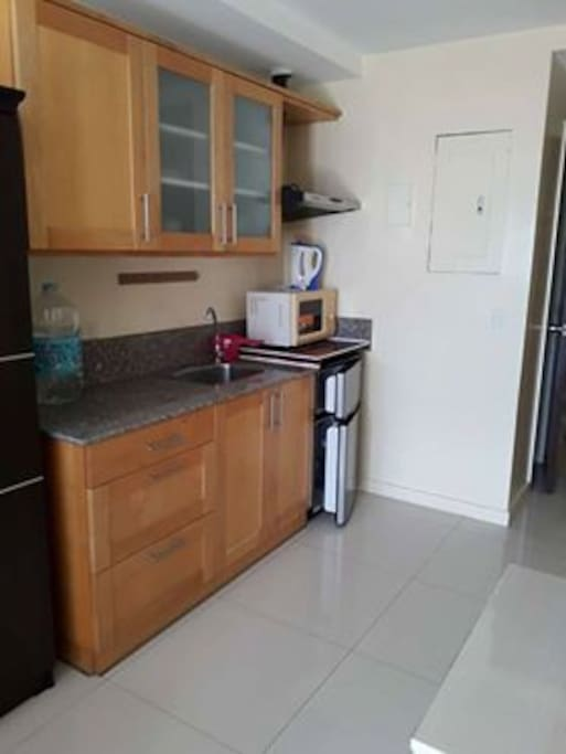 Kitchen with double door fridge, microwave, electric burner, water boiler, range hood, plates, spoon, plates, cups, drinking glasses, etc.