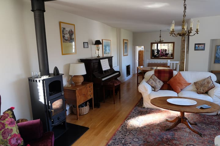 Large lounge with wood-burning stove, piano, TV and ample seating