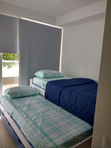 cuarto con doble cama y balcón