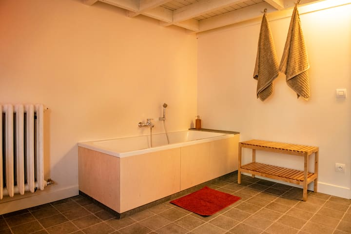 Relax in the large bathtub with central tap and drain.