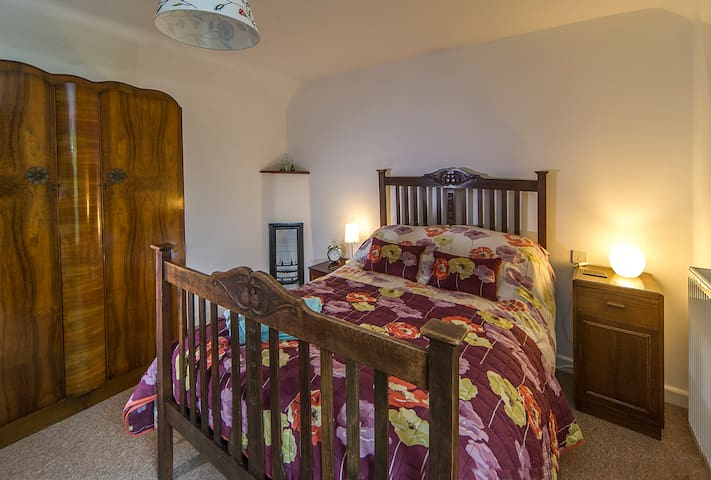 Bedroom with comfortable antique double bed and en-suite bathroom.  That's a tiny, original fireplace in the corner!