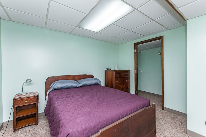 Lower bedroom with full size bed, dresser, closet