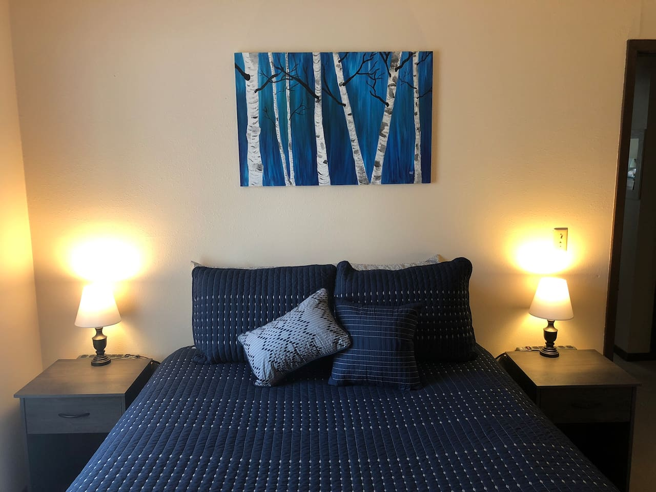 Queen bed with nightstands, built-in power strips on each side and bed side lighting.