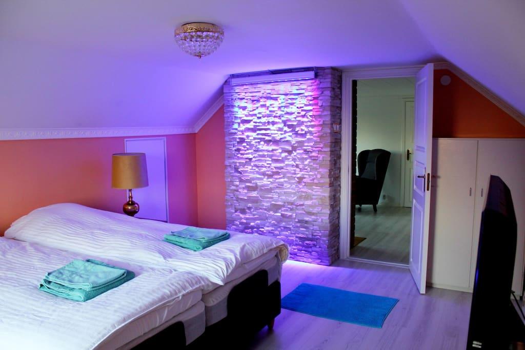 Sovrummet med fri utsikt över landskapet på övervåningen med två enskilda sängar av Hästens med fjärrkontroll. Tv finns i sovrummet.