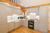 Kitchen with fridge/freezer, dishwasher, cooker, microwave, slow cooker & general kitchen utensils.