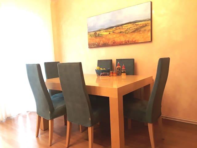 Dining room with brand-new furniture and original artwork showing the countryside near Villafranca del Penedes.  There are a total of eight matching chairs in the house.