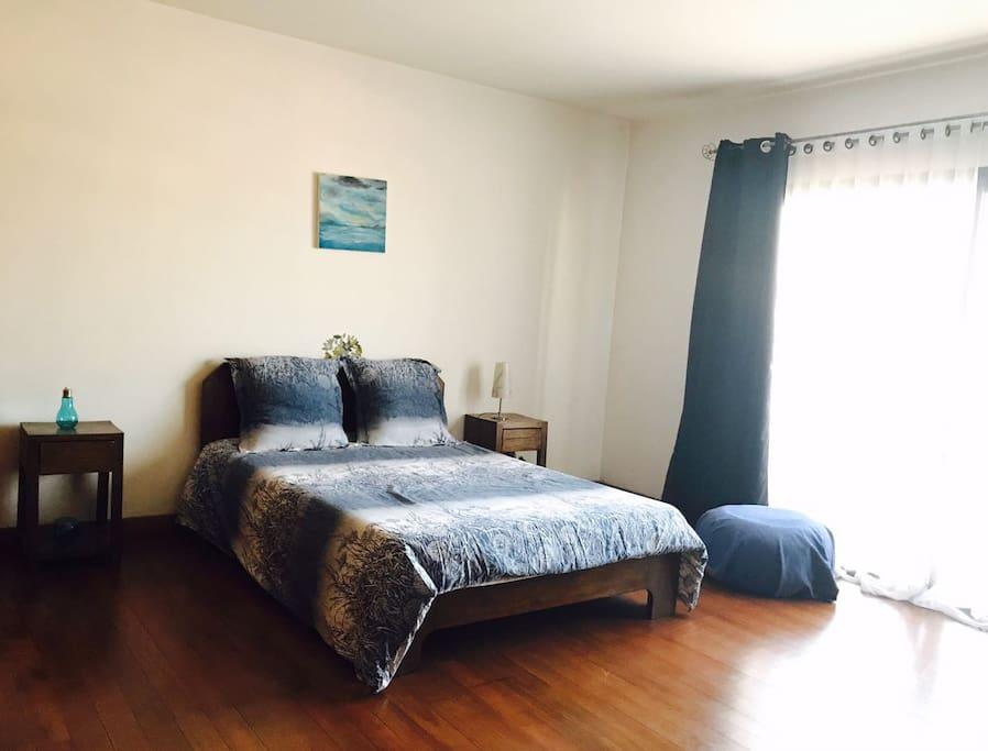 une chambre lumineuse avec un grand lit, dans des tons bleus