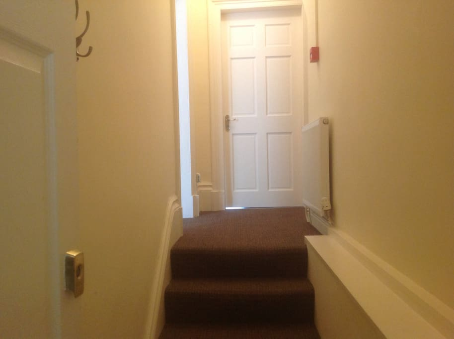 Entrance to apartment with bedroom to the left and open plan lounge and kitchen straight ahead.