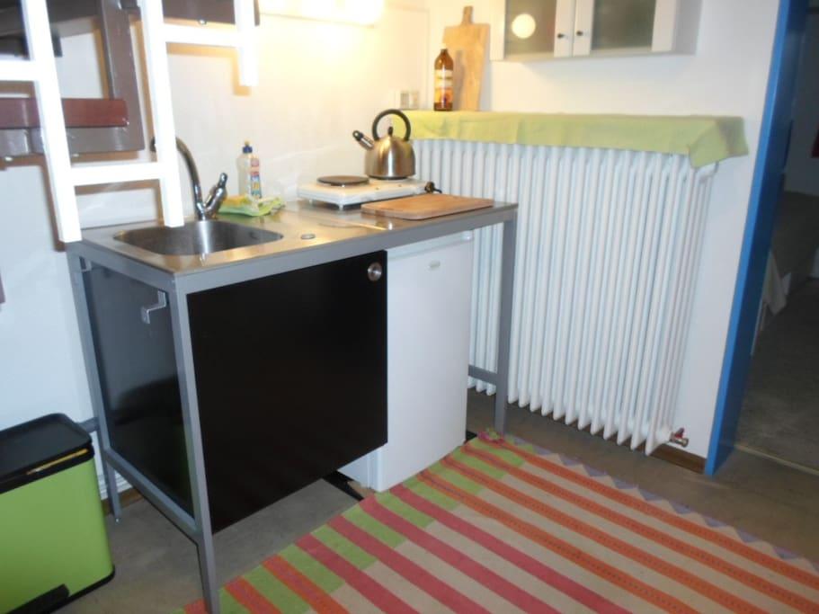 kleine Küchenzeile mit Kühlschrank, Kochplatten, Kaffeemaschine, Geschirr