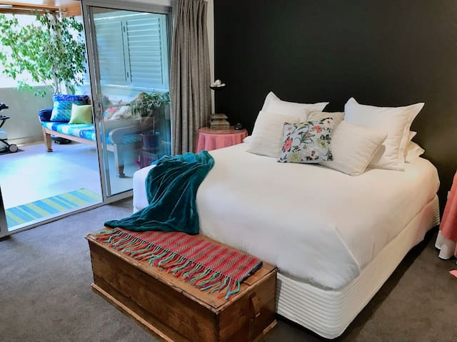 Luxury linens, king size bed and access to the balcony from the spacious bedroom