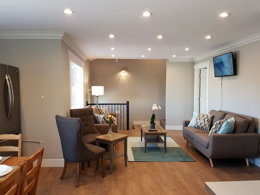 Spacious  living-room with comfortable sofas to relax and watch TV after an exhausting day .