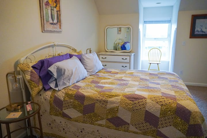 The spacious bedroom features a queen bed and a nice view of the horses and mini-donkeys.