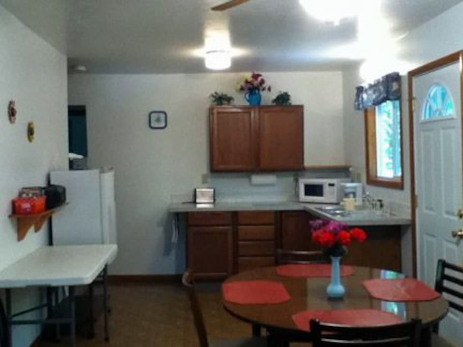 kitchen with efficiency refrigerator, microwave, coffee pot, and dishes