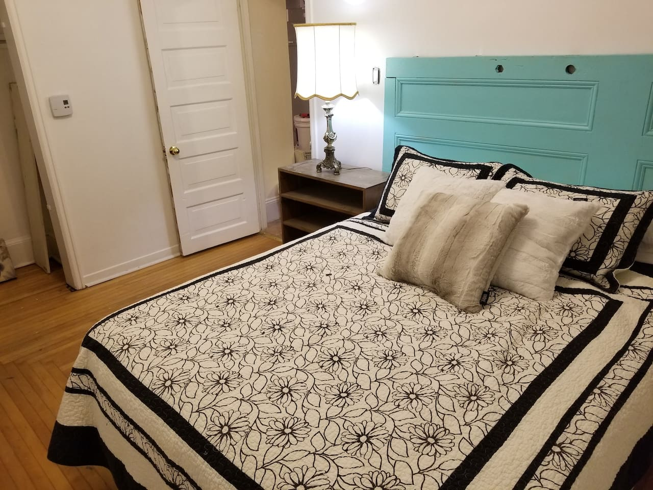 A lot of care was put into every detail of this apartment. Note the headboard is a refurbished hardwood door brought back to life with a bold splash. It rests above a super comfy, brand new queen sized bed.