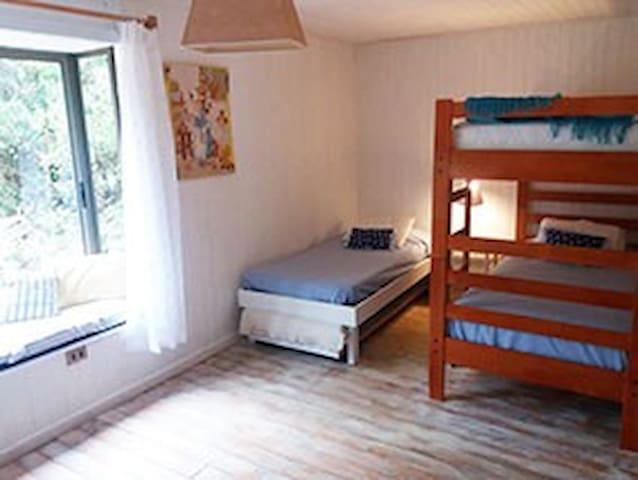 Pieza con una cama nido, un camarote, closet, cómoda y bowindow.