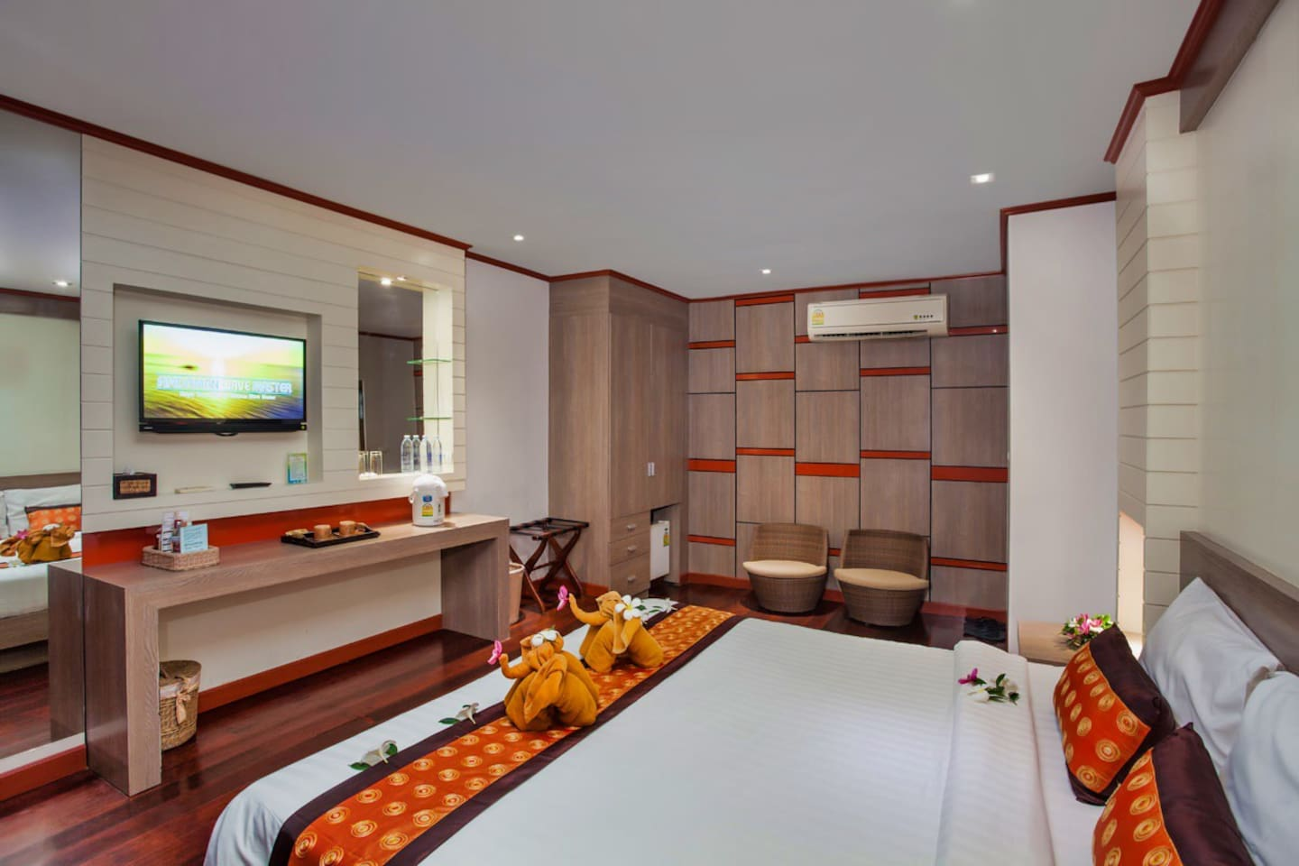 Bedroom with television, airconditioning, seat area and mini fridge.
