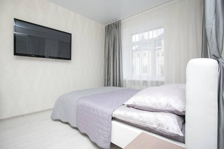 Удобная двуспальная кровать перед большим телевизором с большим количеством каналов