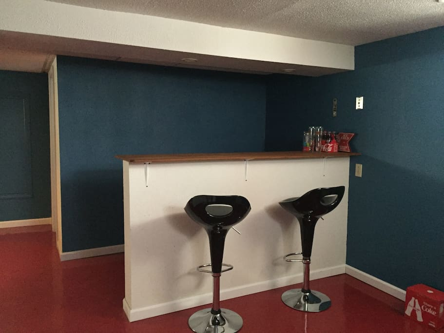 Bar in basement adjacent to full kitchen including refrigerator and stove.