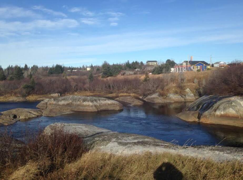 maison bleue à droite en surplomb de la rivière