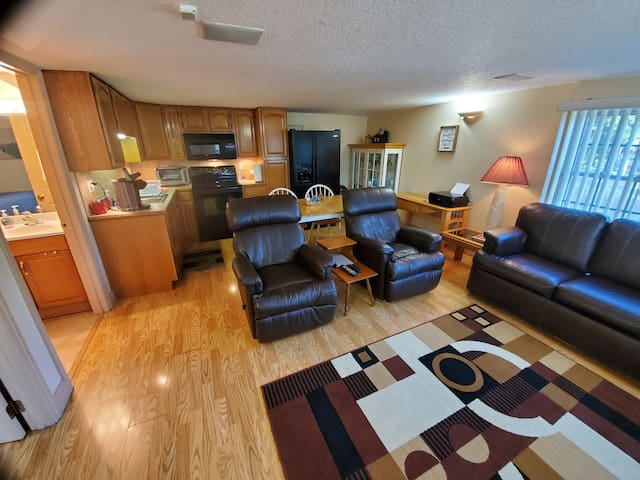 View as you enter. Couch shown on right is a queen-size sleep sofa. see other photos. The kitchen showed at back left  Includes full-size Range, Refrigerator, disposal, microwave, toaster oven, and a Keurig coffee maker.