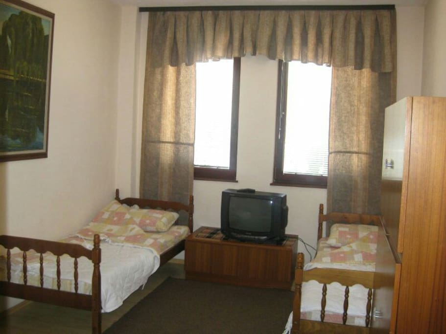 room with three beds and cable TV